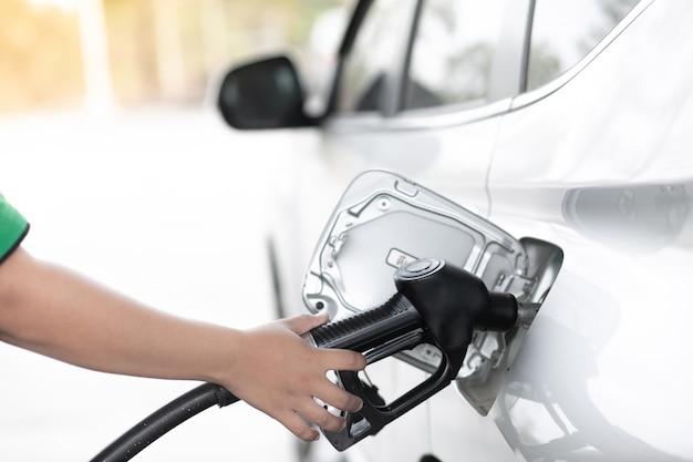 Tankować samochody przy pompie paliwa. trzymaj dyszę paliwa, aby zatankować. instalacja tankowania pojazdów.