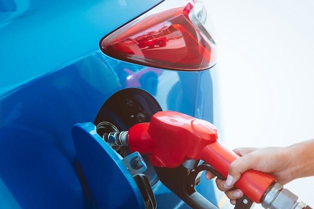 Tankowanie samochodu na stacji benzynowej. uzupełnij paliwo benzyną. pompa paliwa napełniająca dyszę paliwa w zbiorniku paliwa samochodu na stacji benzynowej. przemysł i obsługa paliwowa.