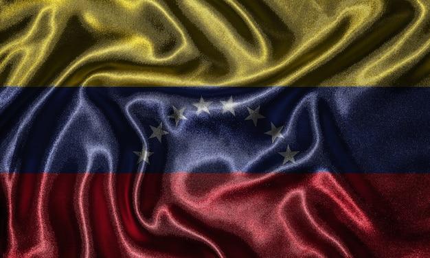 Tapeta flaga wenezueli i macha flagą przez tkaniny.