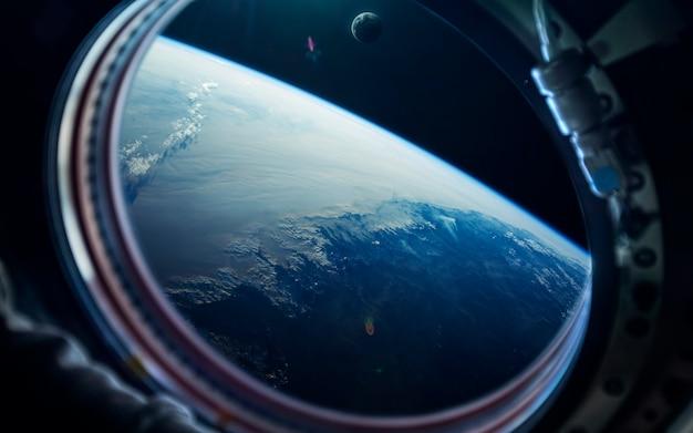 Tapeta kosmiczna science fiction, niebieska ziemia z okna stacji kosmicznej.