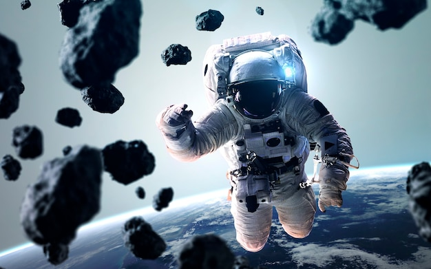 Tapeta kosmiczna science fiction z astronautą na spacerze. elementy tego zdjęcia dostarczone przez nasa