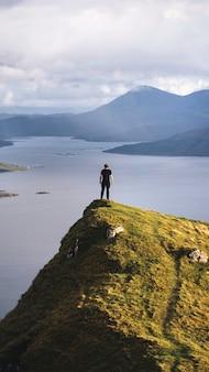 Tapeta na telefon komórkowy z mężczyzną stojącym na wyspie skye w szkocji