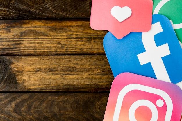 Tapetuje cięcie outs ogólnospołeczne networking ikony z jak ikona na drewnianym stole