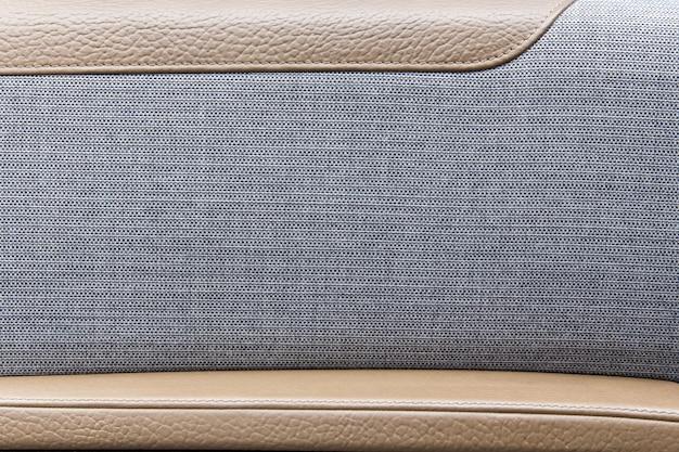 Tapicerka drzwi z szarej tkaniny i skóry w luksusowym samochodzie.