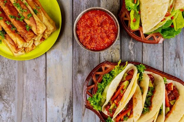 Taquitos, miękkie tortille i salsa na drewnianym stole