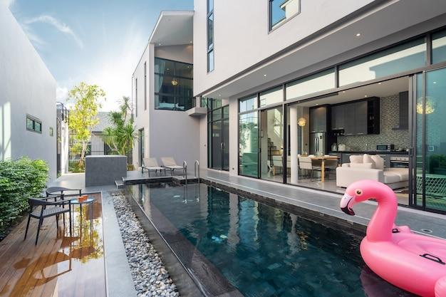 Taras przy basenie i różowa pływająca kaczka w basenie infinity