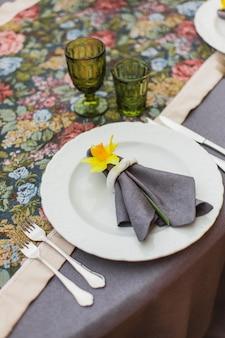 Taras restauracyjny urządzony i stół z kwiatami i świecami na romantyczną kolację weselną