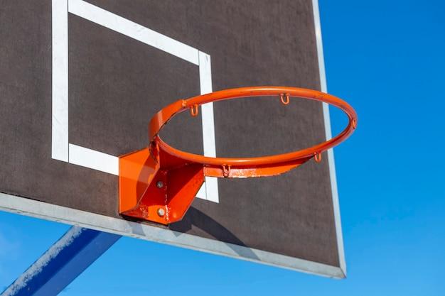 Tarcza koszykówki z czerwonym pierścieniem na tle błękitnego nieba. zdjęcie wysokiej jakości