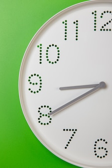 Tarcza zegara ściennego ze zbliżeniem ręki minutowej i godzinowej