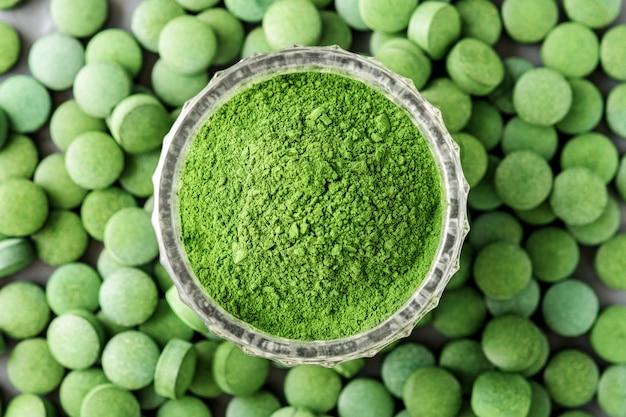 Tarta chlorella lub spirulina w szklanej filiżance na tle tabletu. widok z góry.