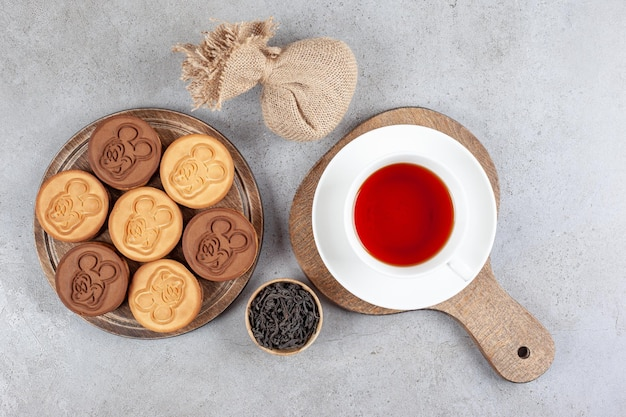 Tarta ciasteczka i filiżanka herbaty na deskach obok małej miski liści herbaty i worek na marmurowym tle. wysokiej jakości zdjęcie