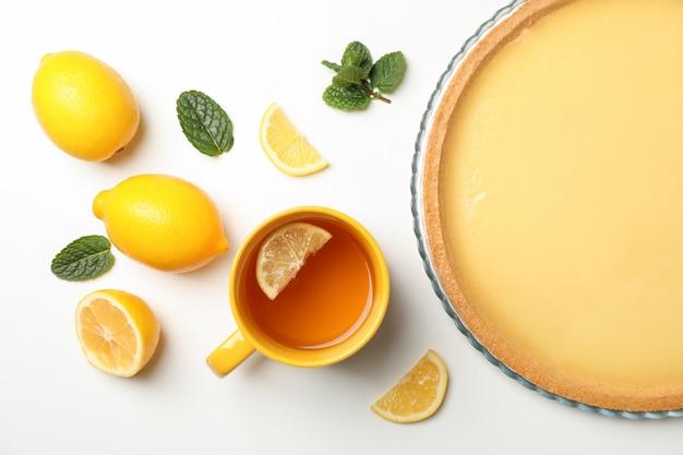 Tarta cytrynowa, mięta, filiżanka herbaty i cytryny na białym, widok z góry