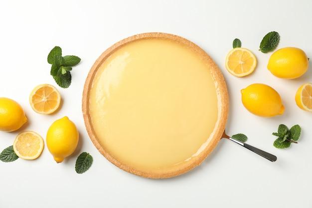 Tarta cytrynowa, mięta i cytryny na białym, widok z góry
