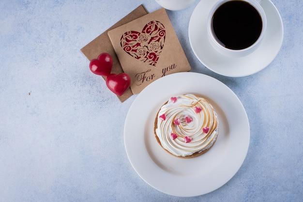 Tarta cytrynowa z bezą i filiżanką kawy, mleko z dekoracjami świątecznymi na walentynki