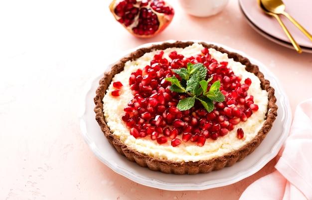 Tarta czekoladowa z kremem kokosowym i granatem i miętą na różowym tle stołu. domowy deser. widok z góry