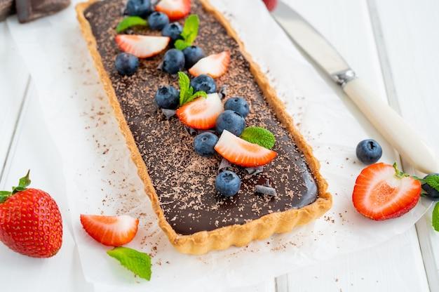 Tarta czekoladowa ze świeżymi jagodami i truskawkami na wierzchu. letni deser.
