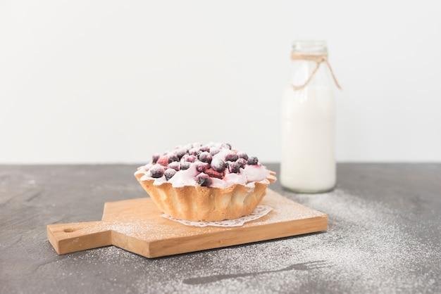 Tarta domowe pyszne jagody na desce do krojenia z butelką mleka
