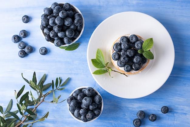 Tarta jagodowa i dojrzałe jagody w misce na niebieskim tle.