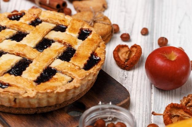 Tarta jagodowa na drewnianej desce na białym drewnianym stole