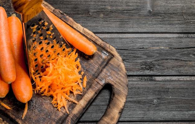 Tarta marchewka na desce do krojenia z tarką. na drewnianym tle