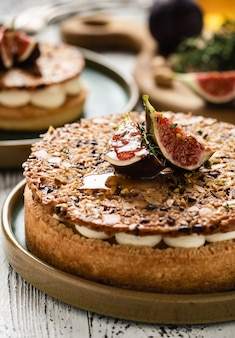 Tarta na bazie piasku ze świeżymi figami, migdałami i chrupiącym waflem z migdałami i proszkiem kakaowym. tarta ze świeżych owoców domowej roboty z jagodami