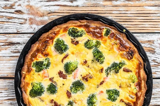 Tarta quiche z wędzonym łososiem, brokułami i szpinakiem. białe drewniane tło. widok z góry.