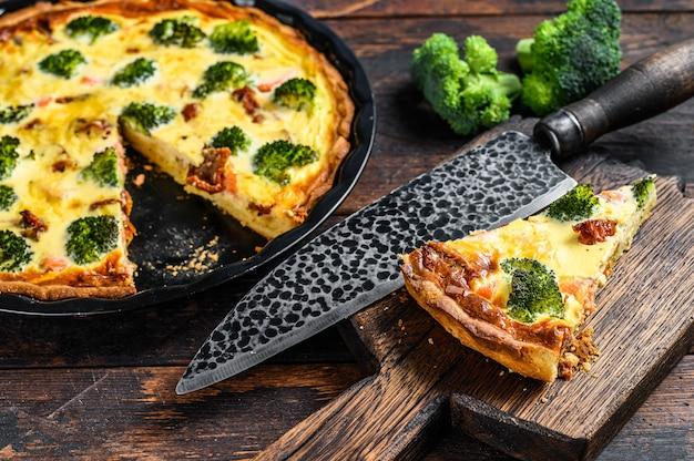 Tarta quiche z wędzonym łososiem, brokułami i szpinakiem. ciemne drewniane tło. widok z góry.