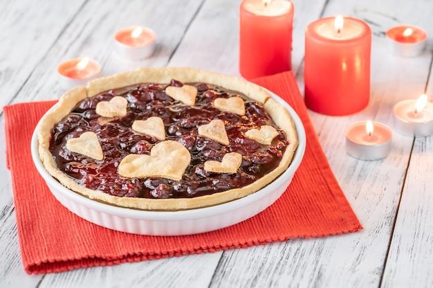Tarta z konfiturą wiśniową ozdobiona sercami, z płonącymi świecami