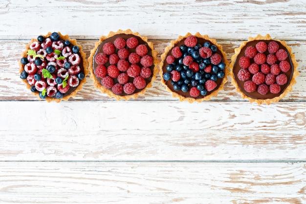 Tarta z malinami i jagodami z ganache czekoladowym, świeżymi jagodami i liśćmi mięty