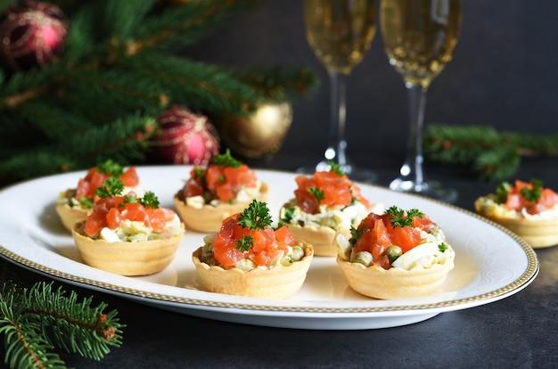 Tartaletki nadziewane sałatką i łososiem na noworocznym stole. świąteczny stół z lampką szampana