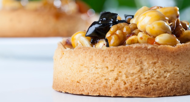 Tartaletki orzechowe pokryte warstwą cukrowego karmelu, deser z ciasta, tartaletki z nadzieniem z orzechów laskowych, orzeszków ziemnych i włoskich oraz suszonych owoców śliwek i moreli