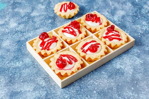 Tartaletki z nadzieniem z białej czekolady i konfiturą jagodową na wierzchu.