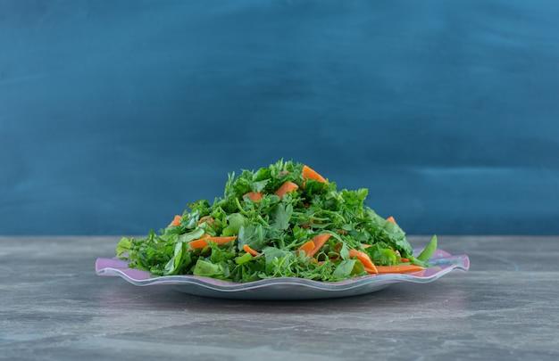 Tarte warzywa na talerzu, na marmurowym stole.