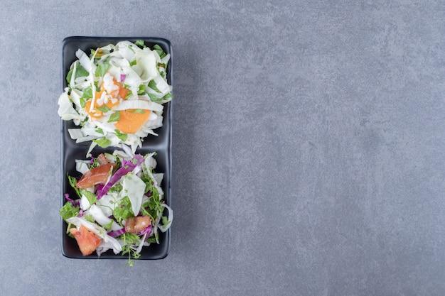 Tarte warzywa w misce, na marmurowej powierzchni.