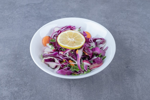 Tarte warzywa z cytryną na talerzu, na marmurowej powierzchni.
