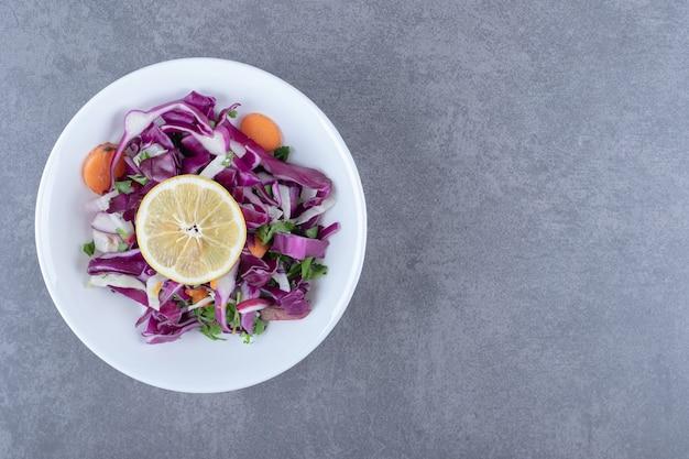 Tarte warzywa z cytryną na talerzu, na marmurowym tle.