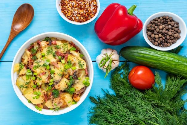 Tartiflette z boczkiem, ziołami i warzywami na drewnianym niebieskim stole. widok z góry.