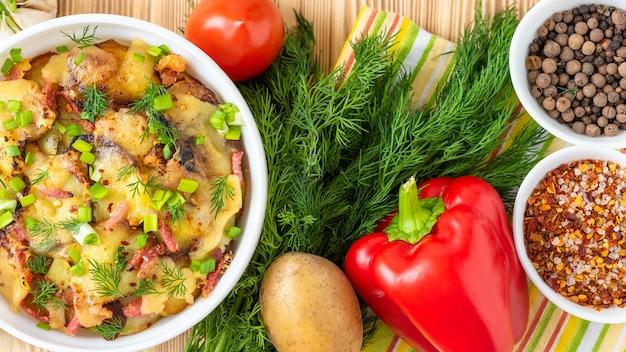 Tartiflette z warzywami i boczkiem na drewnianym stole. widok z góry.