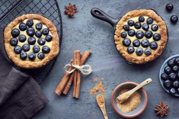 Tartlets pyszne jagody z kremem waniliowym na ciemnej powierzchni teksturowanej