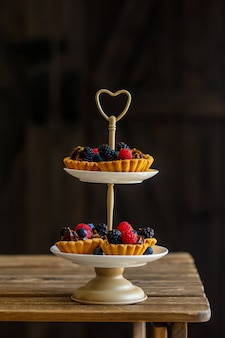 Tartlets z jagodami i kremem czekoladowym na stojaku