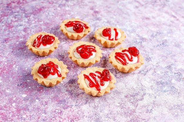 Tartlets z nadzieniem z białej czekolady i konfiturą jagodową na wierzchu.