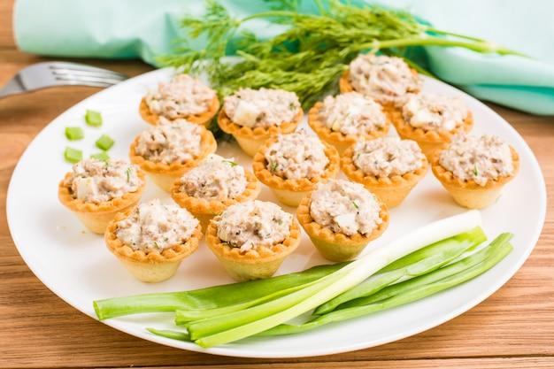 Tartlets z sałatką z ryb, jajek i zieleni na talerzu