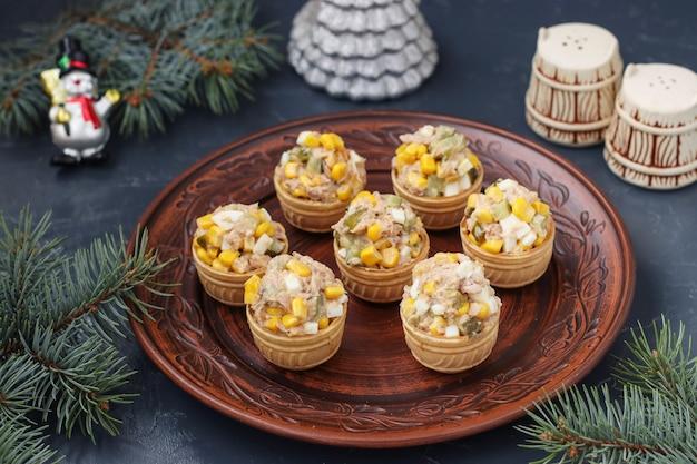 Tartlets z tuńczykiem, kukurydzą i jajkami na talerzu na ciemnym stole, format poziomy, zbliżenie