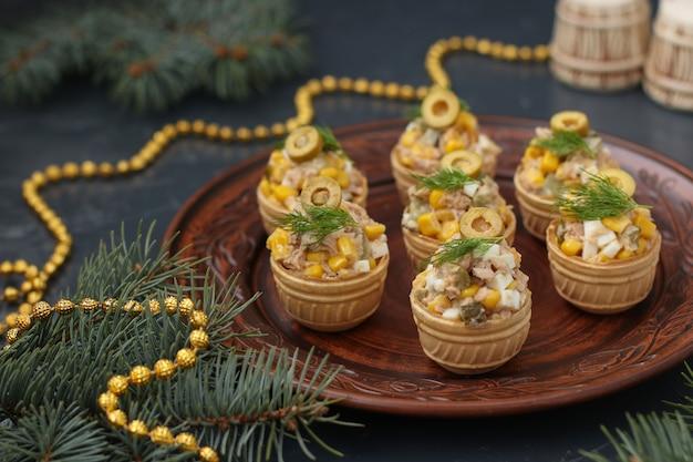 Tartlets z tuńczykiem, kukurydzą i jajkami na talerzu na ciemnym tle