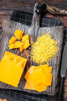 Tarty i pokrojony w kostkę ser cheddar na drewnianej desce do krojenia. ciemne drewniane tło. widok z góry.