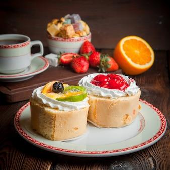 Tarty owocowe z truskawkami i pomarańczą oraz filiżanka herbaty w talerzu