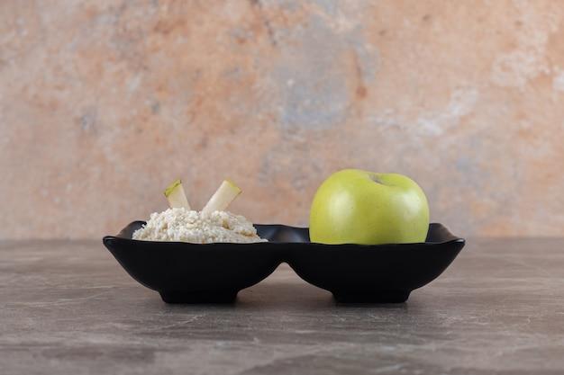 Tarty placek ryżowy i jabłko w misce, na marmurowej powierzchni