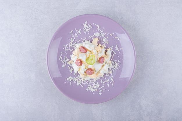 Tarty ser i jajko z kiełbaskami na fioletowym talerzu.