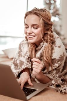 Tarzanie się na łóżku. nieskazitelna wesoła kobieta pisząca na klawiaturze laptopa, leżąc na łóżku w pustych mieszkaniach