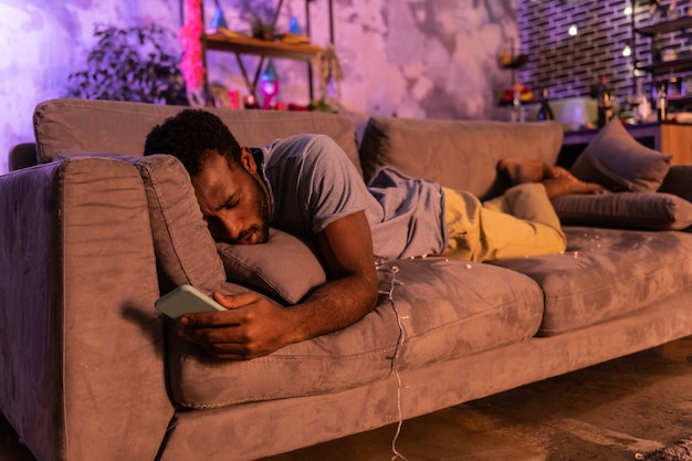 Tarzanie się popcornem. chory afroamerykanin czuje się źle i opiera się na poduszce na kanapie z ekstremalnym kacem po imprezie alkoholowej